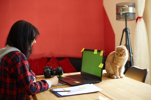 Fotografo femminile creativo con simpatico gatto, utilizzando tavoletta grafica e penna stilo, lavorando alla scrivania e ritoccando foto su computer tablet, ritoccatore sul posto di lavoro in studio fotografico home office con animali