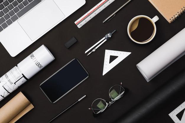 Disposizione piana creativa della tabella nera degli architetti con i modelli del rotolo