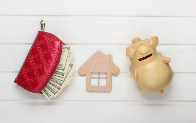 Creative flat laici composizione. statuetta di casa, salvadanaio, portafoglio con soldi su un tavolo bianco.