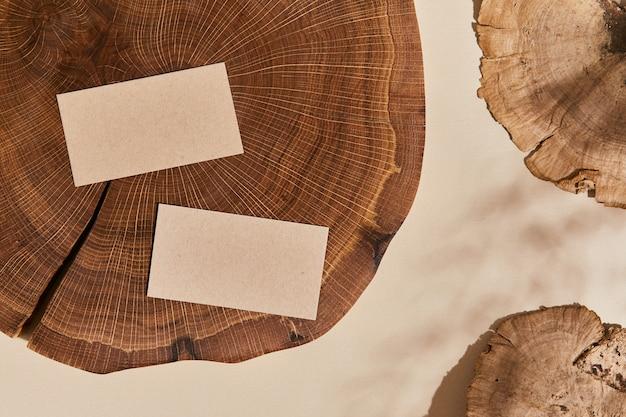 Composizione creativa piatta con biglietti da visita simulati, legno, materiali naturali e accessori. colori neutri, vista dall'alto, modello.