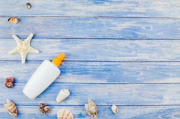Creative flat lay concept vacanze estive di viaggio. vista dall'alto di conchiglie e stelle marine mockup bottiglia di protezione solare su sfondo blu pastello plance di legno copia spazio in stile rustico, testo modello di cornice