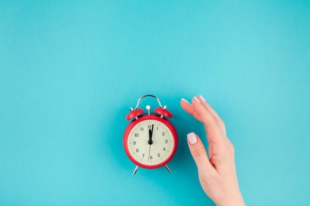 Creative flat lay concept vista dall'alto della mano della donna che tiene la sveglia vintage rossa sul turchese blu brillante