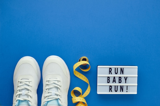 Disposizione piatta creativa di attrezzature per lo sport e il fitness e lightbox con slogan sportivo. sneakers bianche da donna, metro a nastro.