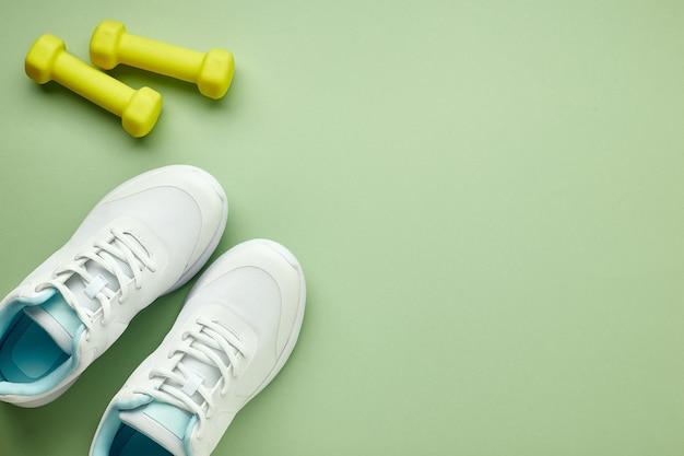 Disposizione piatta creativa di attrezzature sportive e per il fitness. scarpe da ginnastica bianche da donna e manubri verdi su un pavimento verde chiaro.