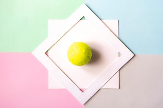 Disposizione creativa del piano con il bal di tennis isolato nel telaio bianco sul fondo di colore, concetto creativo f di idea