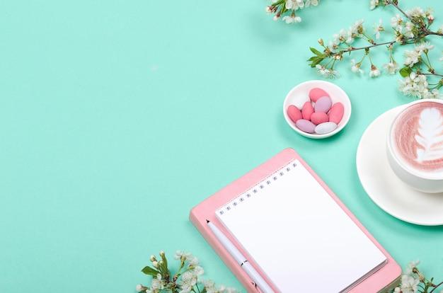 Piatto creativo laici della scrivania dell'area di lavoro, blocco note per la lista dei desideri e oggetti di stile di vita su sfondo verde