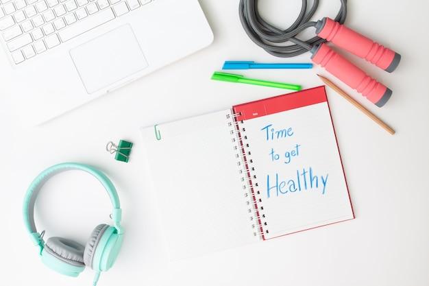 La disposizione piatta creativa della scrivania dell'area di lavoro con laptop, cuffie e allenamento
