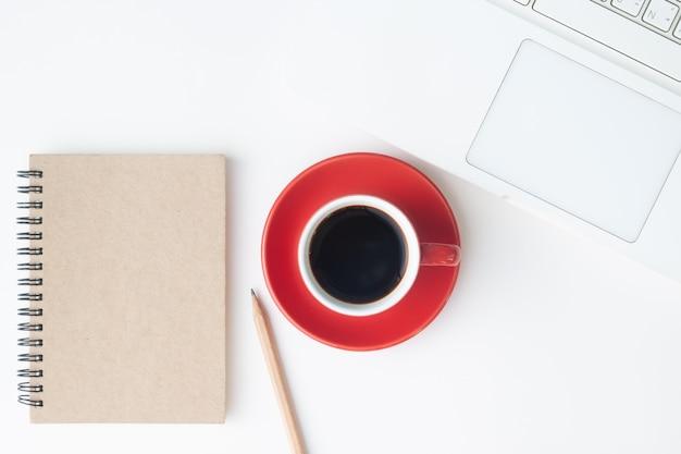 Disposizione piatta creativa della scrivania dell'area di lavoro con il taccuino rosso della tazza di caffè, del computer portatile e del diario.
