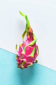 Creativo layout piatto con dragonfruit (pitaya o pitahaya) su carta bicolore bicolore, bianco e blu. vista dall'alto di tutto il frutto esotico sano maturo fresco intero.