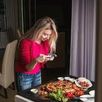 Blogger di fotografia di cibo creativa che scatta foto sul cellulare