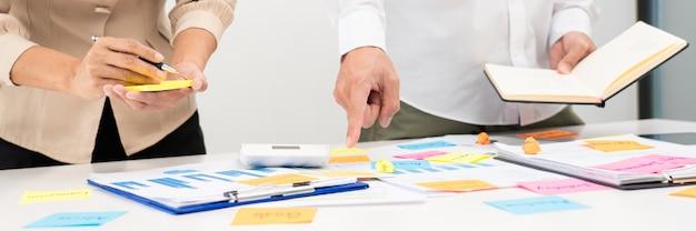 Un gruppo creativo di uomini d'affari che fa il brainstorming utilizza note adesive per condividere l'idea sul tavolo o sul tavolo in ufficio