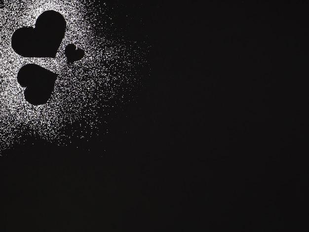 Forma di cuore creativa fatta di polvere bianca, cuori isolati su sfondo nero, cuori di zucchero, buon san valentino
