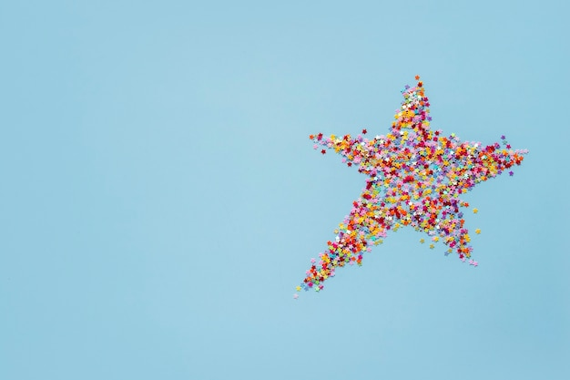 Concetto di vacanza creativa: forma a stella realizzata con mini stelle di colore su sfondo blu