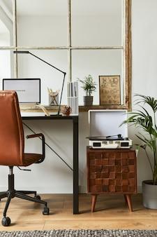 Composizione creativa per l'home office del moderno design d'interni maschile con scrivania industriale nera, poltrona in pelle marrone, laptop, giradischi vintage e accessori personali eleganti. modello.