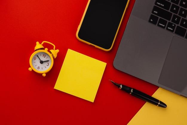 Luogo di lavoro domestico creativo con penna nera, clcok e nota adesiva gialla, posto per il testo. lavora dal concetto di casa.