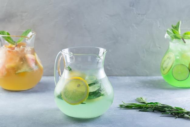Idea creativa. composizione. limonata di colore diverso in caraffe di vetro con frutta e menta fresca