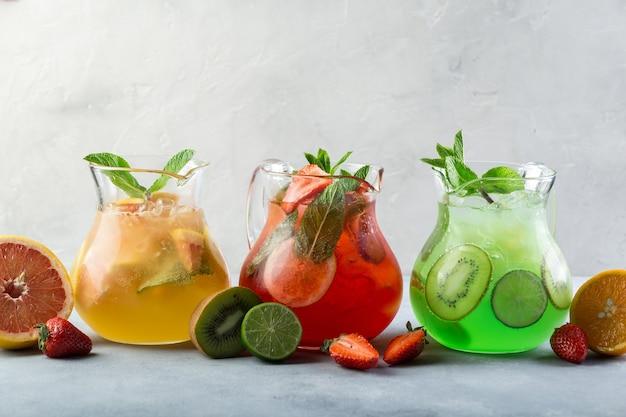 Idea creativa. composizione. limonata di colore diverso in caraffe di vetro con frutta e guarnita con menta fresca e frutta a fette sul tavolo.