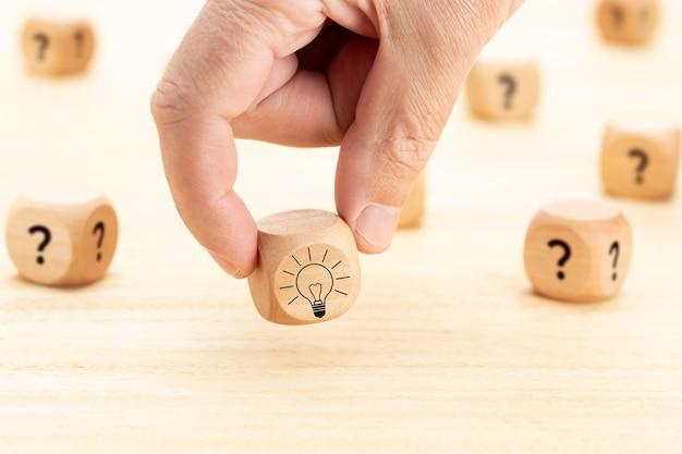 Idea creativa o concetto di innovazione. blocchetto di cubo di legno selezionato a mano con il simbolo del punto interrogativo e l'icona della lampadina sulla tavola di legno