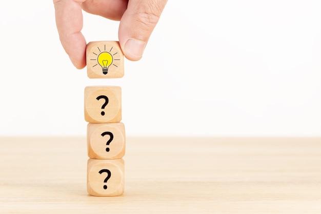 Idea creativa o concetto di innovazione. blocchetto di cubo di legno selezionato a mano con il simbolo del punto interrogativo e l'icona della lampadina.