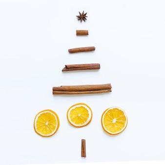 Immagine creativa dell'albero di natale fatto a mano fatto di anice stellato, bastoncini di cannella, fette d'arancia essiccate su superficie bianca. anno nuovo concetto. lay piatto.