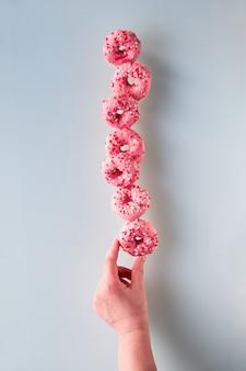 Immagine creativa di perfetto equilibrio, torre o piramide di gustose ciambelle rosa in equilibrio sulla ciambella inferiore in mano femminile. popolare dessert chanukah. equilibrio concettuale.