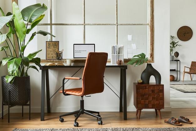 Composizione interna creativa del moderno design maschile dell'area di lavoro dell'ufficio domestico con scrivania industriale nera, poltrona in pelle marrone, laptop e accessori personali eleganti. modello.