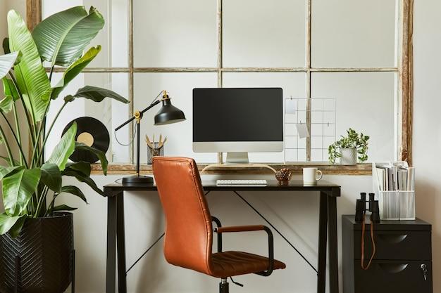 Composizione interna creativa del moderno design maschile dell'area di lavoro dell'ufficio domestico con scrivania industriale nera, poltrona in pelle marrone, pc e accessori personali eleganti. modello.