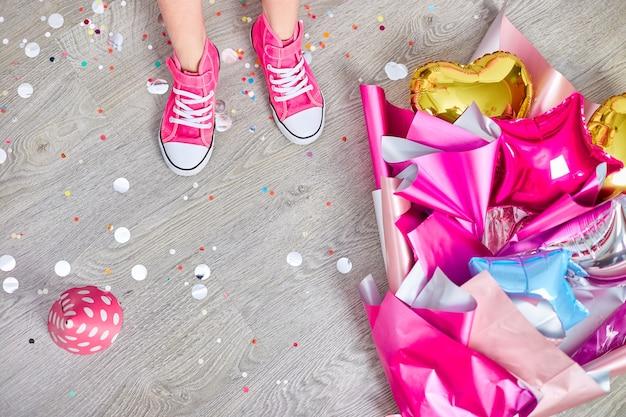 Disposizione creativa della gamba funky della ragazza in scarpe da ginnastica rosa e vestito, composizione di compleanno piatta. copia spazio. concetto di festa di compleanno.