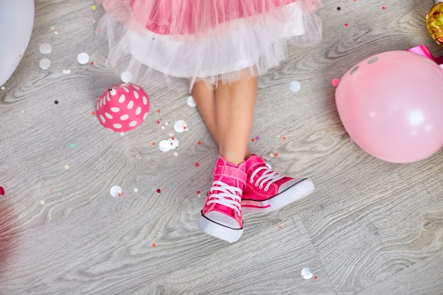 Disposizione creativa della gamba funky della ragazza in scarpe da ginnastica rosa e vestito, disposizione piatta