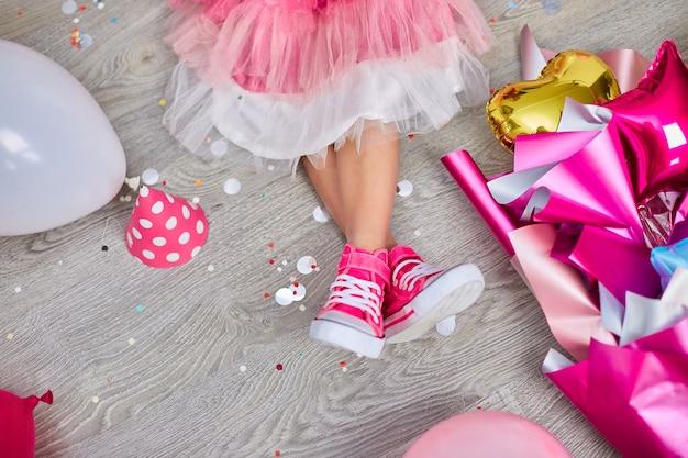 Disposizione creativa della gamba funky della ragazza in abito e scarpe da ginnastica rosa