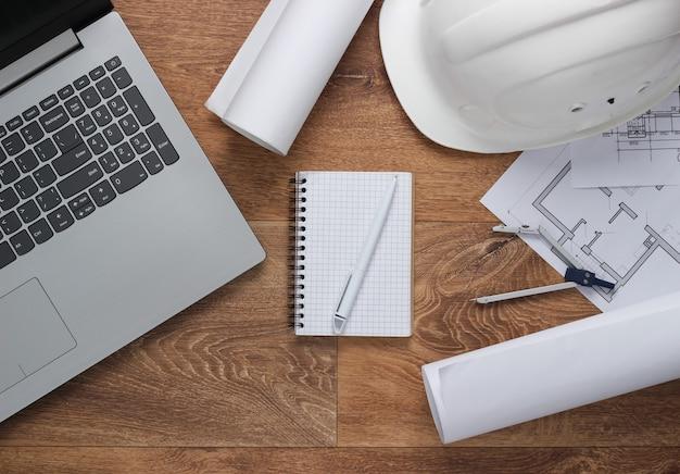 Layout creativo di architetti con disegni a rullo, piano del progetto architettonico, casco da costruzione sul pavimento, area di lavoro con laptop. vista dall'alto. lay piatto