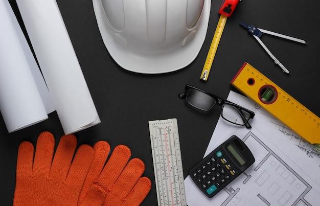Layout creativo di architetti con disegni a rullo, piano di progetto architettonico, strumenti di ingegneria e cancelleria su sfondo nero, area di lavoro. vista dall'alto. lay piatto.