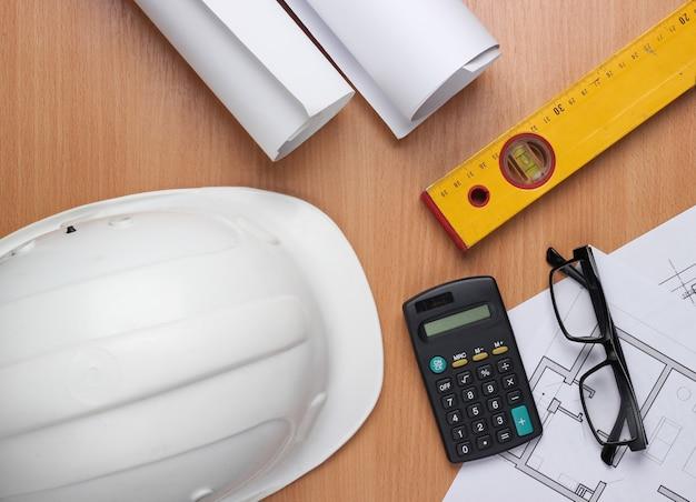 Layout creativo di architetti con disegni a rullo, piano del progetto architettonico, strumenti di ingegneria e cancelleria sul tavolo, area di lavoro. vista dall'alto. lay piatto