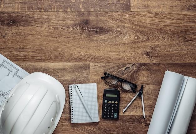 Layout creativo di architetti con disegni a rullo, strumenti di ingegneria e cancelleria sul pavimento, area di lavoro. vista dall'alto. lay piatto. copia spazio