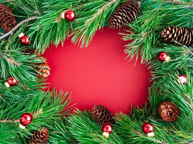Layout creativo di rami di albero di natale e coni su uno sfondo rosso