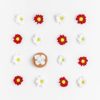 Composizione di layout creativo di fiori e uova di pasqua su sfondo pastello.