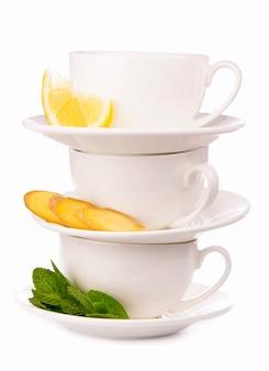 Layout creativo fatto di tazza di tè alla menta, limone, zenzero su uno sfondo bianco. vista dall'alto.