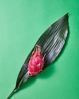 Un layout creativo composto da un frutto intero di pitahaya su una foglia verde su uno sfondo di carta verde. vista dall'alto