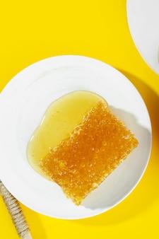 Layout creativo fatto di favi e pozzanghera di miele fresco su sfondo giallo piatto bianco