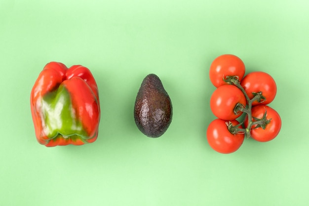 Layout creativo fatto di pepe, avocado e pomodoro. vista piana laico e dall'alto. concetto di cibo.