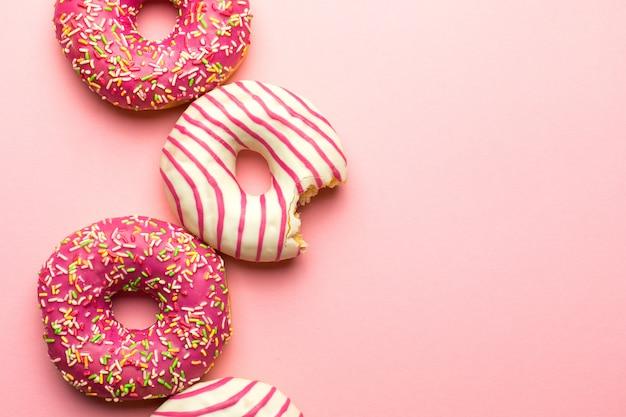 Disposizione creativa fatta di ciambelle glassate rosa. disteso. concetto di cibo. concetto macro. varie ciambelle decorate su morbido sfondo rosa. ciambelle dolci e colorate