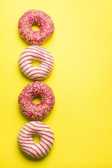 Disposizione creativa fatta di ciambelle smaltate gialle. disteso. concetto di cibo. concetto macro. varie ciambelle decorate su morbido sfondo rosa. ciambelle dolci e colorate