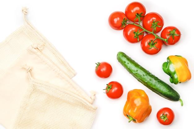 Layout creativo di pomodori, cetrioli, peperoni e sacchetti riutilizzabili in cotone a rete