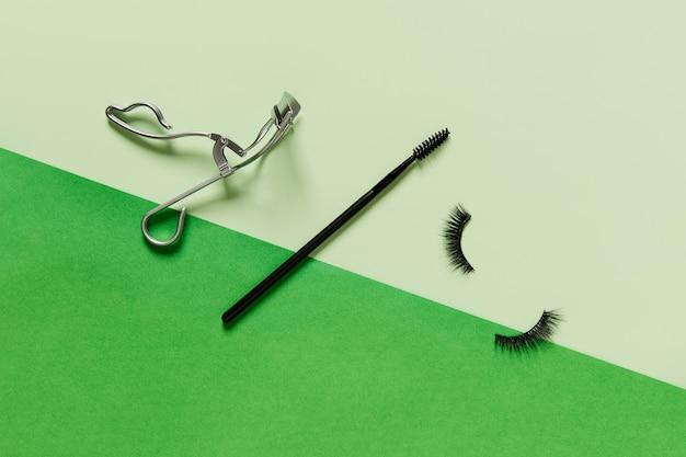Layout creativo con accessori per il trucco su sfondo verde