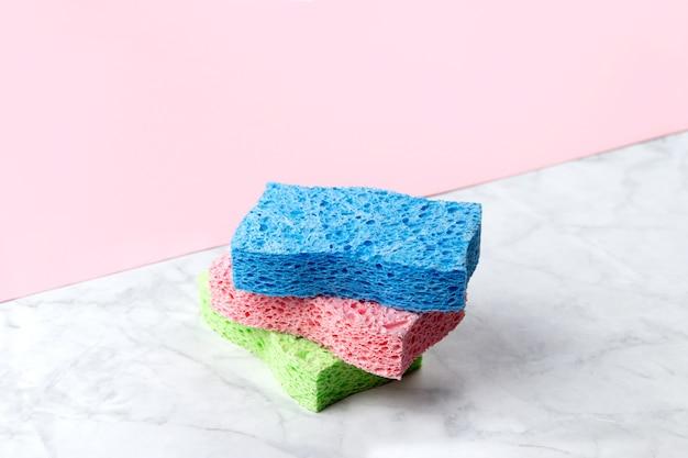 Disposizione creativa con spugne per lavare i piatti su doppio fondo rosa e marmo. modello di servizio di pulizia