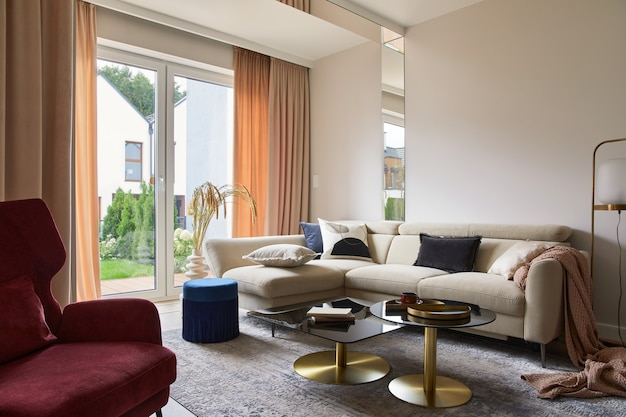Composizione interna creativa del soggiorno con divano beige, tavolino da caffè in vetro, moquette sul pavimento e accessori glamour. modello.