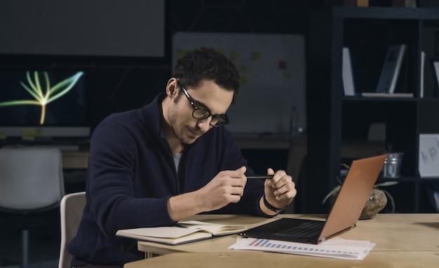 Uomo creativo con gli occhiali che lavora a tarda notte in ufficio
