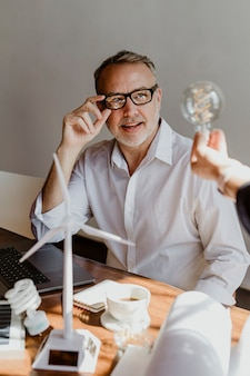 Uomo maturo creativo che guarda una lampadina