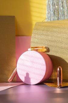 Composizione moderna e creativa di carta oro e rosa con scatola lucida e bottiglie di siero vista frontale
