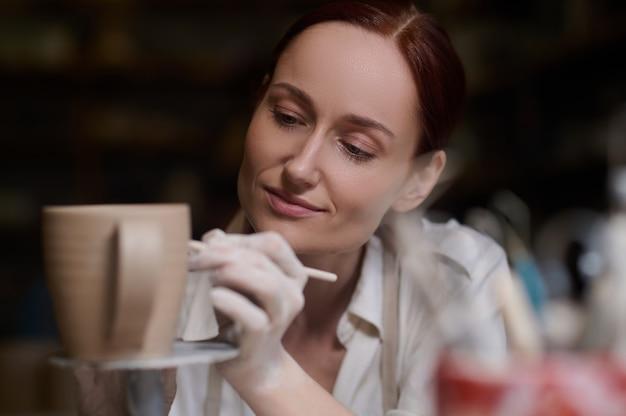 Umore creativo. una giovane donna che dipinge la ceramica e sembra coinvolta
